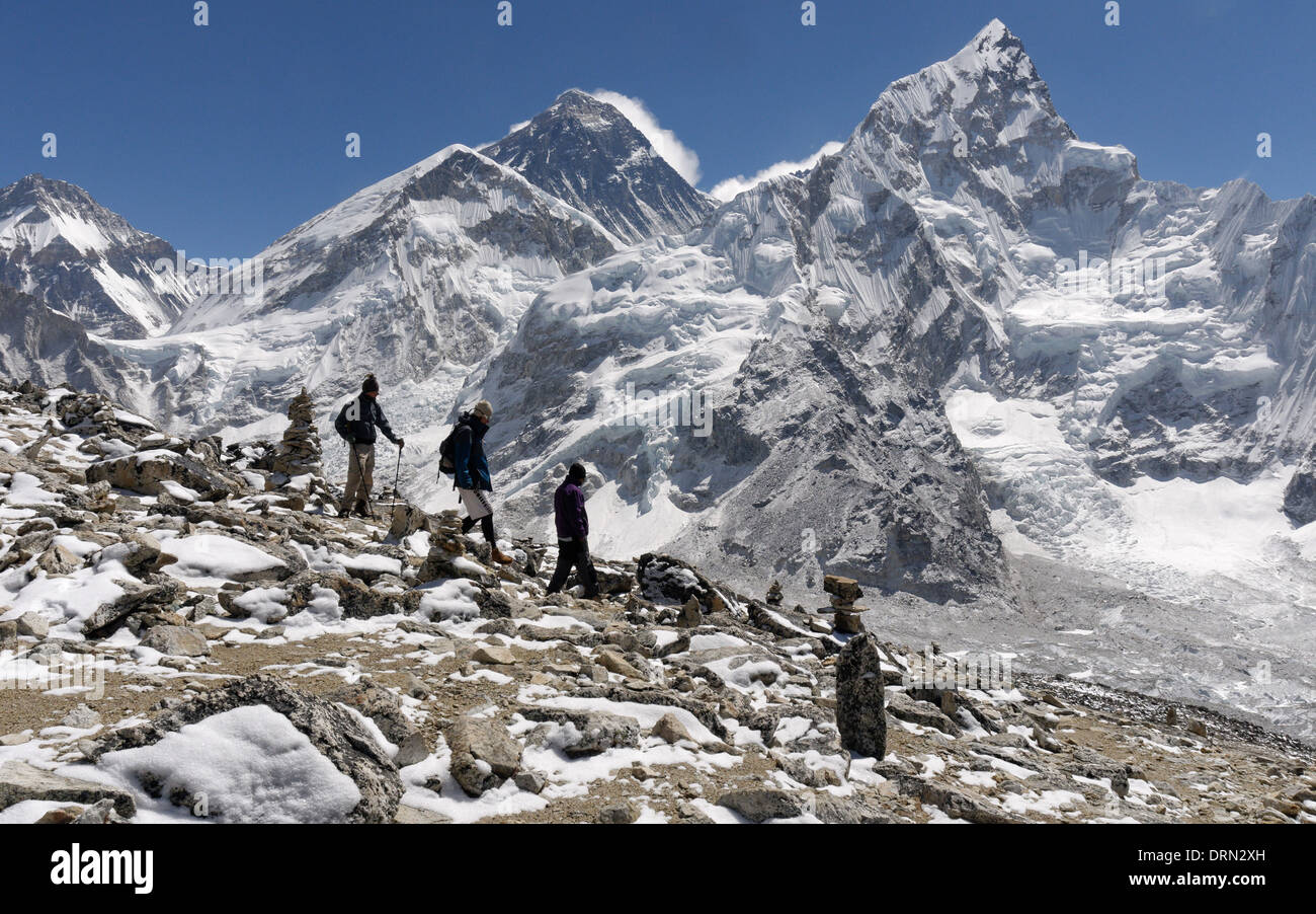 A group of trekkers on the summit of Kala Pattar, the high point of the Everest Base Camp trek, with Mount Everest beyond. - Stock Image
