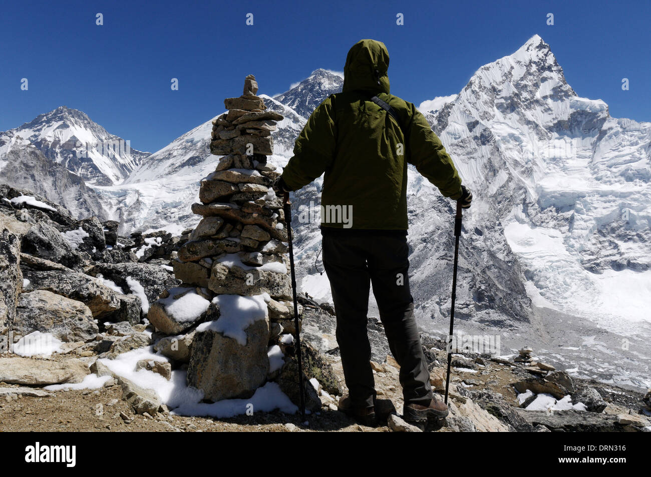 A lady trekker on the summit of Kala Pattar, the high point of the everest base camp trek, with Mount Everest beyond - Stock Image