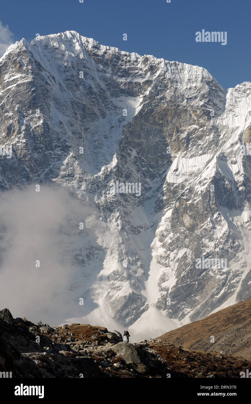 The tiny figure of a trekker is dwarfed by the east face of Taboche on the everest base camp trek - Stock Image
