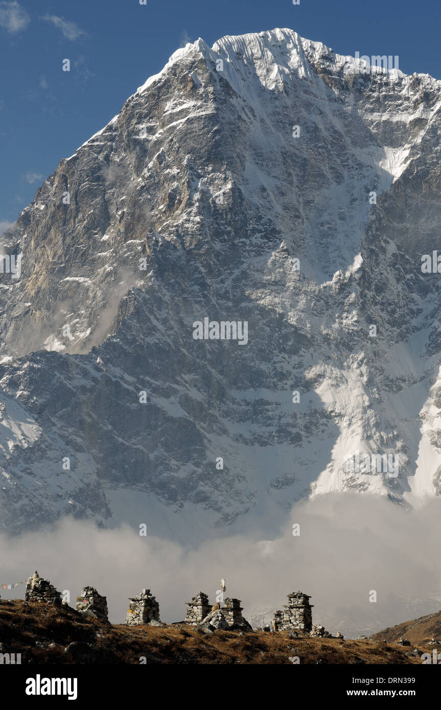 Memorials cairns to Everest's dead, with the east face of Taboche behind - Stock Image