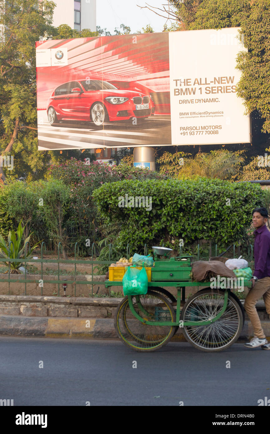 An advert for BMW cars in Ahmedabad; India, contrasting with the poor of the city. - Stock Image