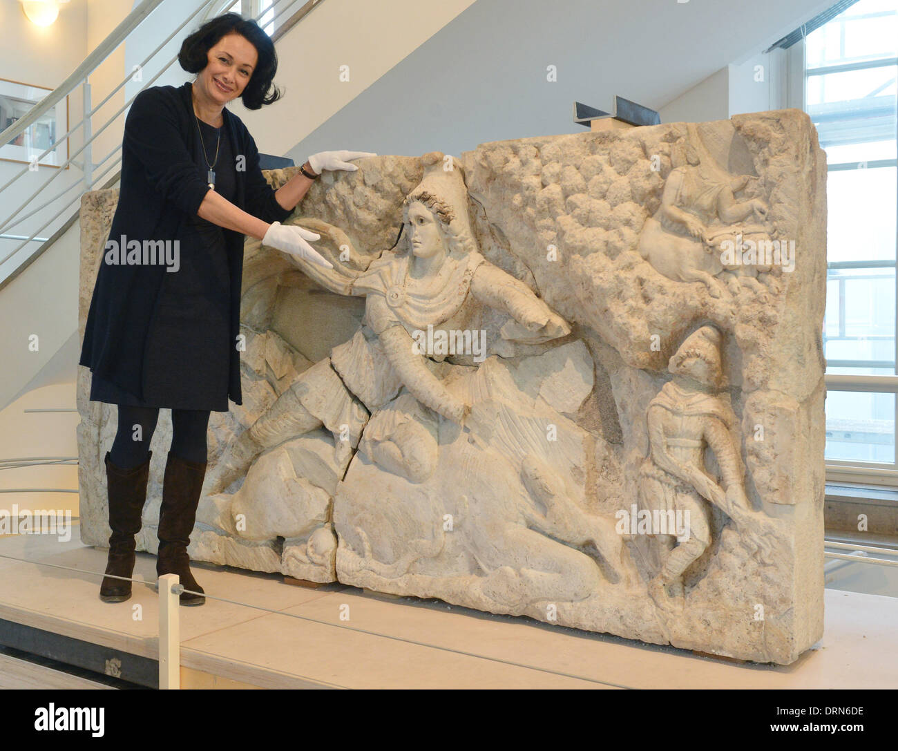 Karlsruhe, Germany. 29th Jan, 2014. ATTENTION PUBLICATION BLOCKING PERIOD THURSDAY 30 JANUARY 2014 4.30 PM Katarina Horst, collection and science manager at Baden State Museum, shows the reconstructed Relief of Mithras of Tor Cervara in Rome in Karlsruhe Palace at the Baden State Museum in Karlsruhe, Germany, 29 January 2014. The relief weighs two tons and was built in 150 AD. The antique artwork was damaged during a bomb attack, and stolen and sold in parts. The Baden State Museum (Badisches Landesmuseum) put the pieces together. Photo: Uli Deck/dpa/Alamy Live News - Stock Image