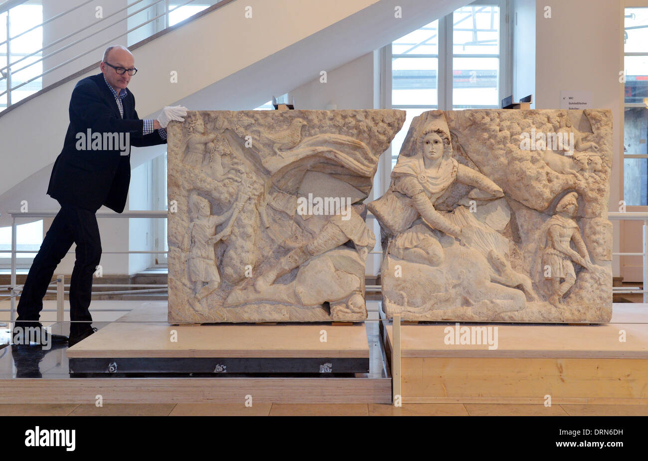 ATTENTION PUBLICATION BLOCKING PERIOD THURSDAY 30 JANUARY 2014 4.30 PM Oliver F. Morr, restoration and conservation manager at Baden State Museum pushes togteher the two pieces of the reconstructed Relief of Mithras of Tor Cervara in Rome in Karlsruhe Palace at the Baden State Museum in Karlsruhe, Germany, 29 January 2014. The relief weighs two tons and was built in 150 AD. The antique artwork was damaged during a bomb attack, and stolen and sold in parts. The Baden State Museum (Badisches Landesmuseum) put the pieces together. Photo: Uli Deck/dpa - Stock Image
