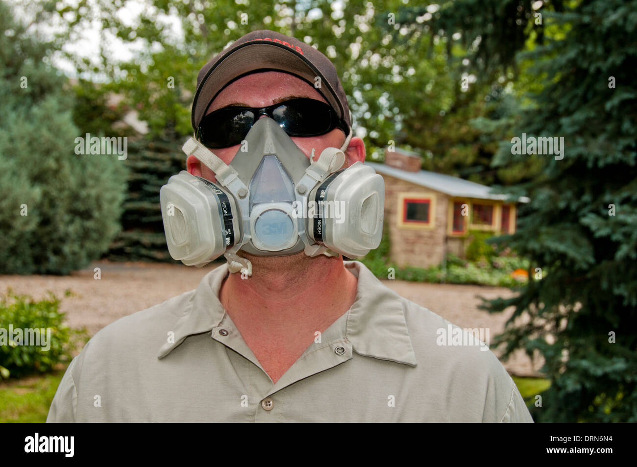 Pesticide/insecticide applicator wearing protective mask - Stock Image