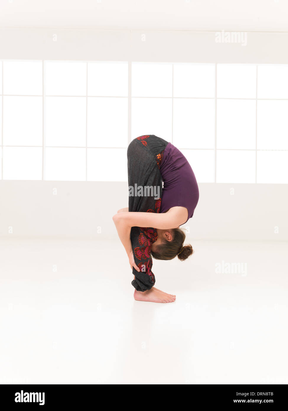 young woman in intermediate yoga pose, face between the legs, full