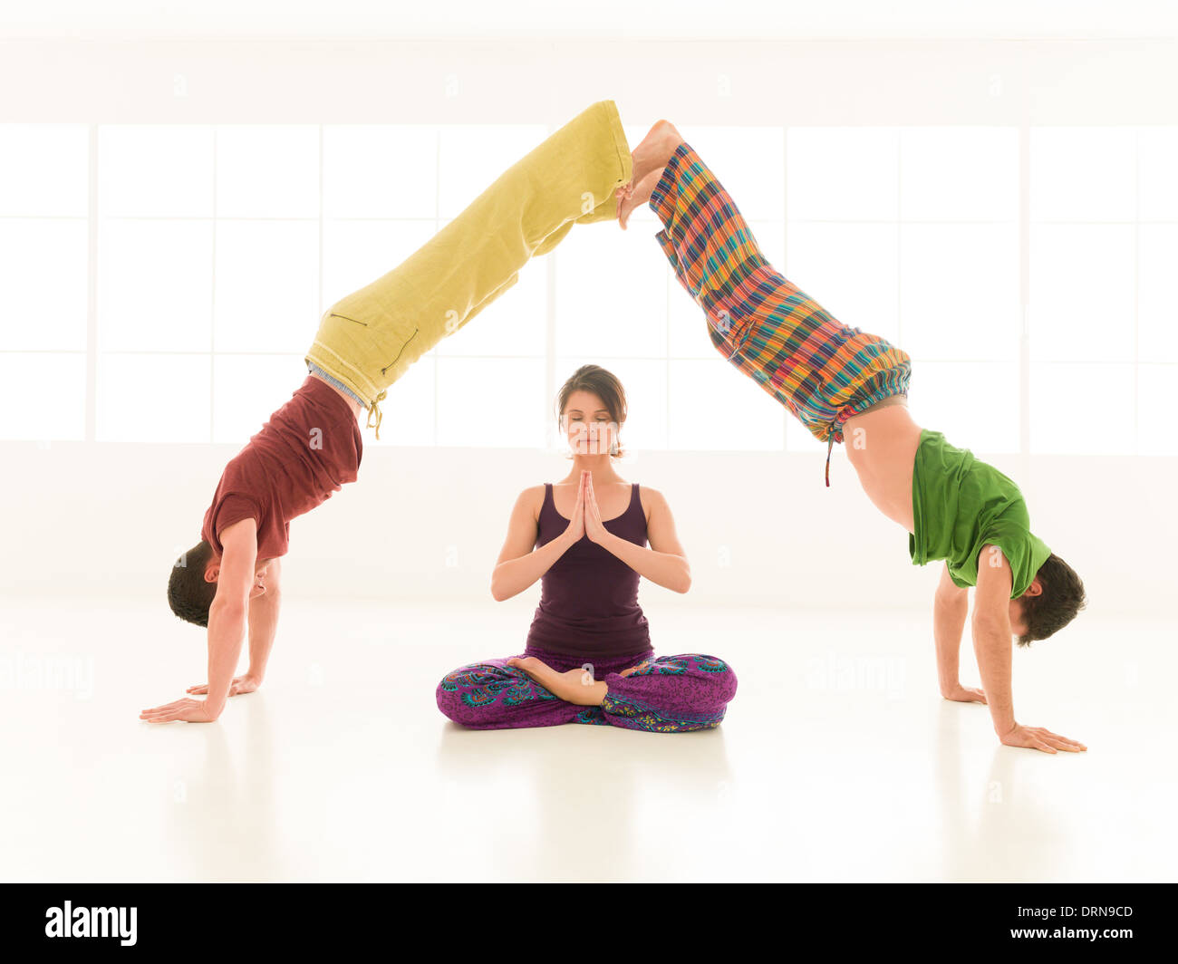 three young people a woman and two men practice yoga partner in