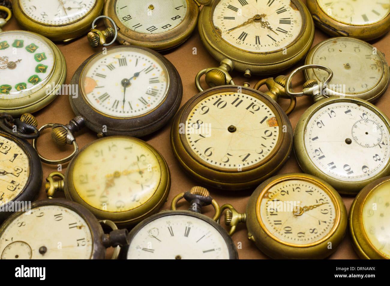 Antique broken clocks on brown background - Stock Image