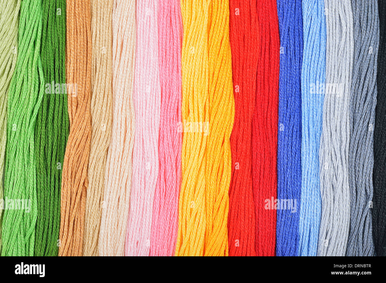 Colorful embroidery threads in a row. Colorful background. - Stock Image