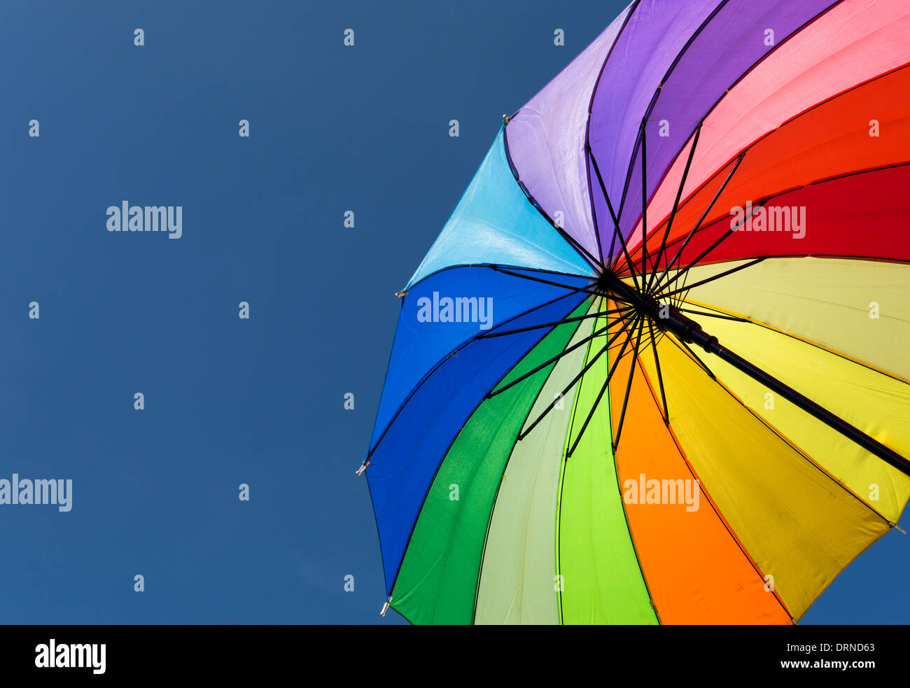 Rainbow coloured Umbrella against blue sky - Stock Image