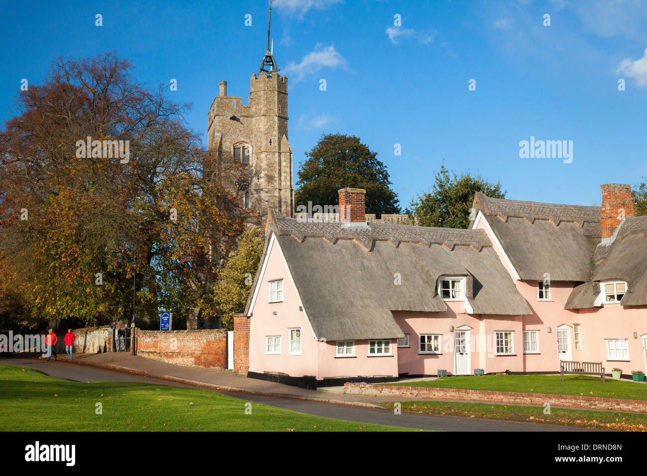 The Pink Cottages beneath St Mary's church, Cavendish, Suffolk, England. - Stock Image