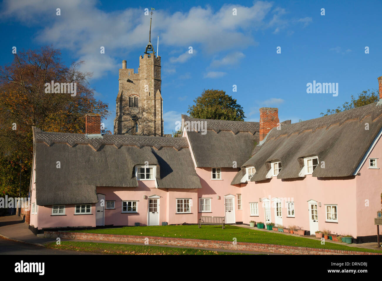The Pink Cottages beneath St Mary's church, Cavendish, Suffolk, England. Stock Photo