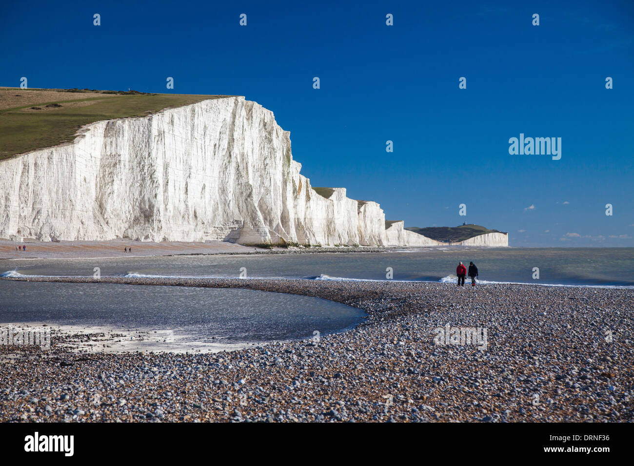 Couple walking beneath the Seven Sisters, Cuckmere Haven Beach, County Sussex, England. Stock Photo