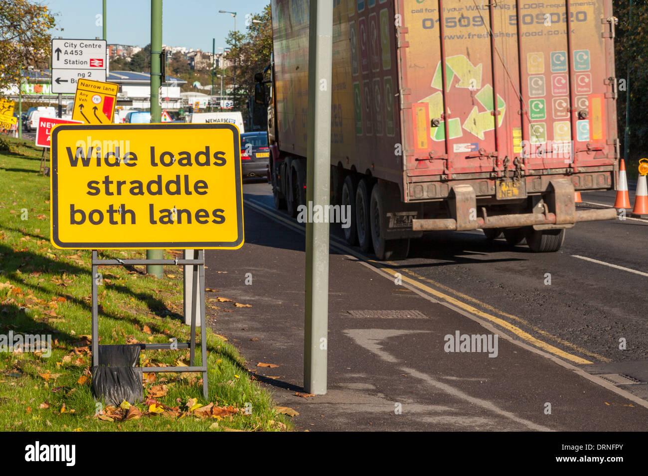 Wide loads straddle both lanes sign at road works, Nottingham, England, UK - Stock Image
