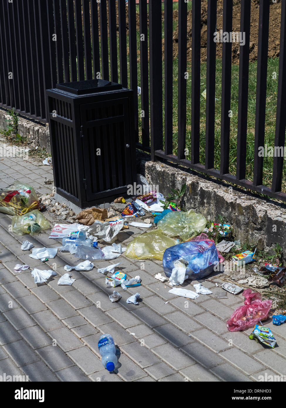 Rubbish on the street next to an empty trash can - Stock Image