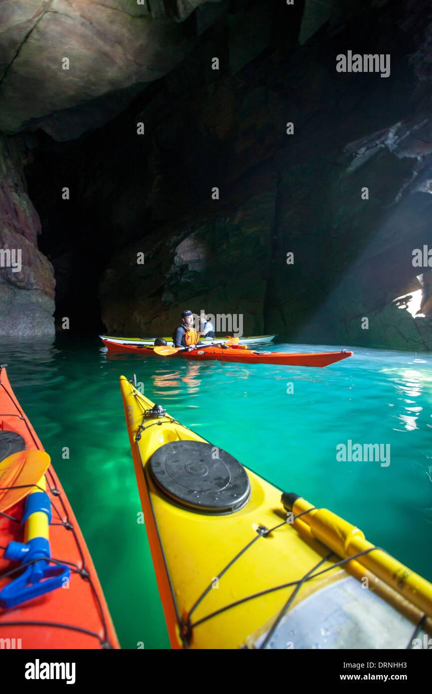 Sea kayakers inside a cave near Doonamoe Point, Belmullet Peninsula, County Mayo, Ireland. - Stock Image