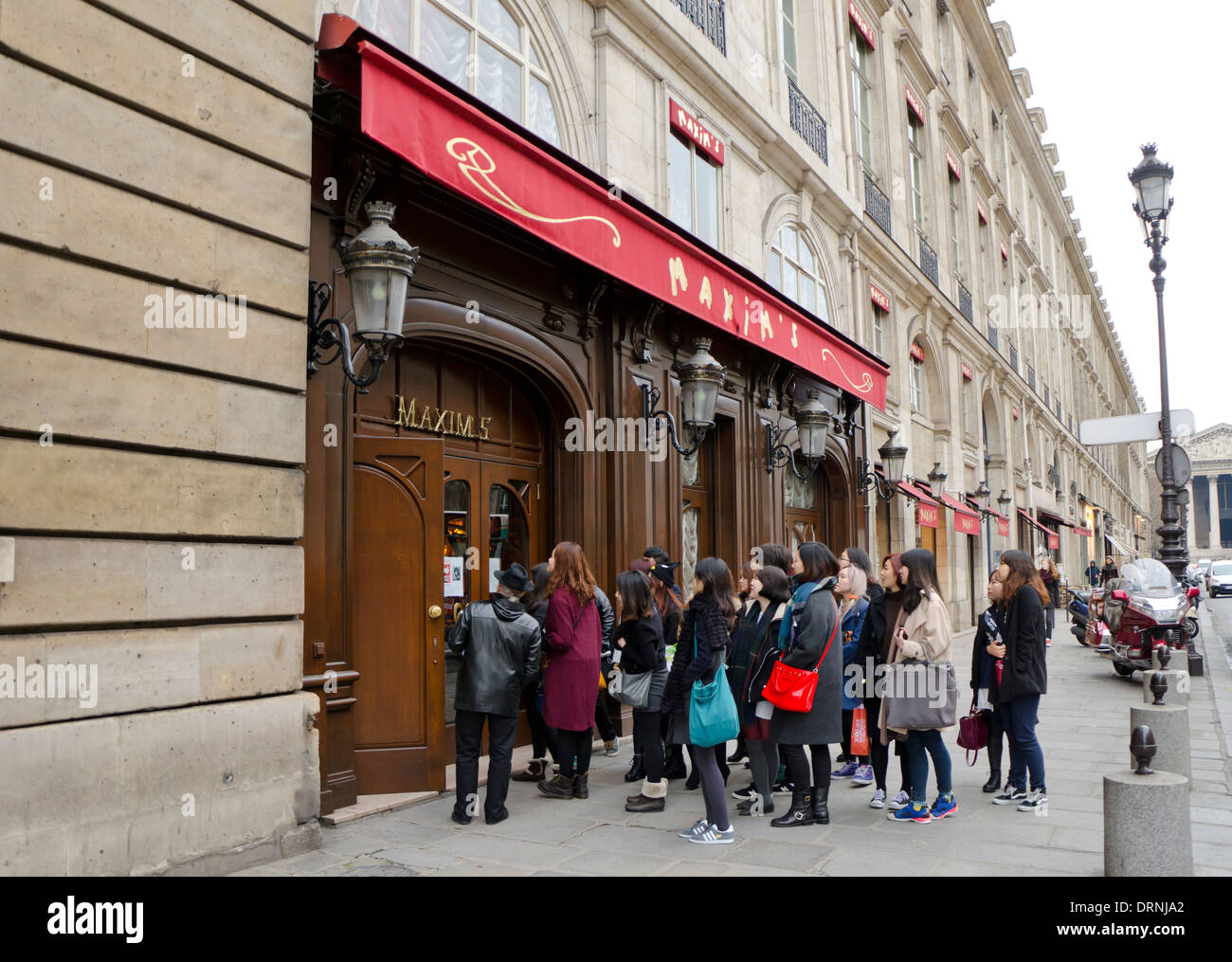 Japanese tourists visiting Maxim's restaurant at Rue Royale in Paris, France. - Stock Image