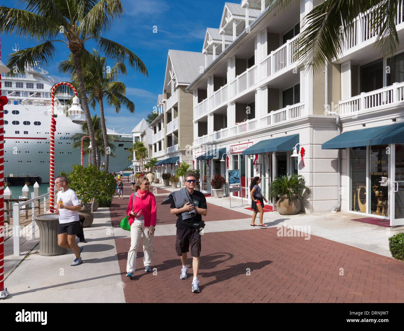 Tourists at Key West, Florida, USA with a cruise ship docked behind - Stock Image