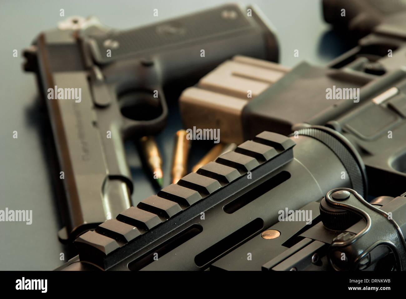 Assorted guns and ammo sitting on dark table - Stock Image