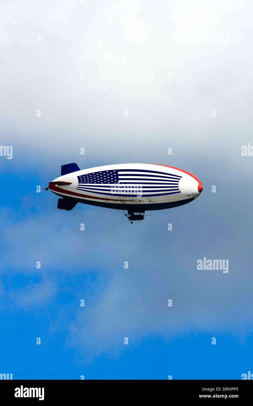 An American Flag toting airship flying around the blue skies of Florida - Stock Image