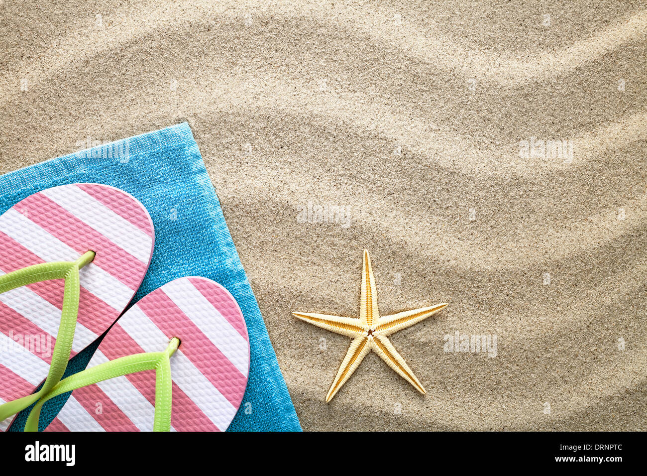 Sand background with towel, flip flops and starfish. Summer concept. Top view - Stock Image