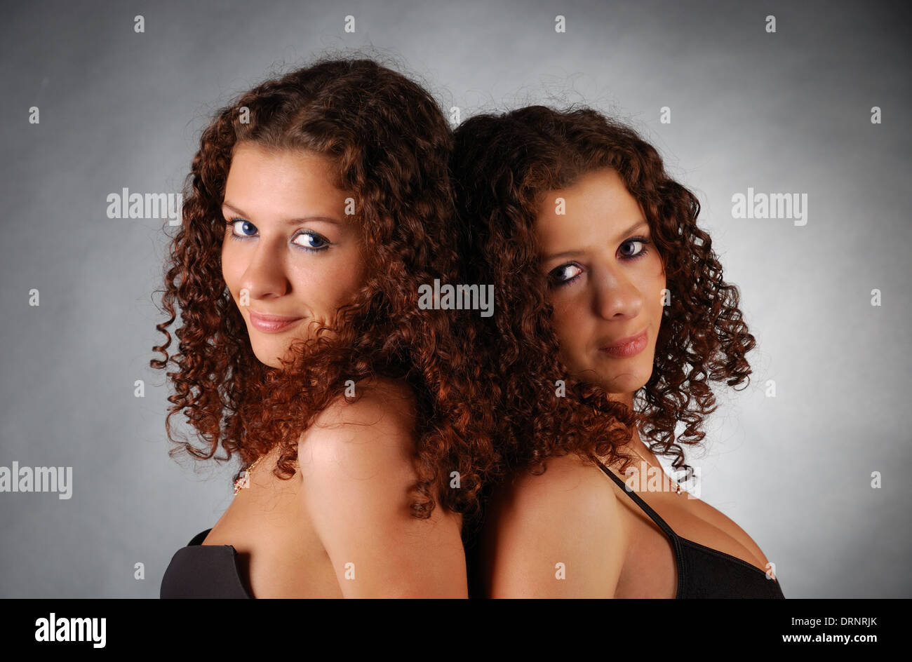 Portrait of twins back to back - Stock Image
