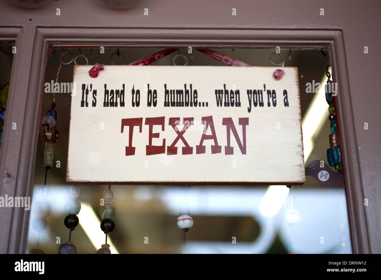 A sign reading 'It´s hard to be humble…when you´re a Texan' decorates a window in South Dallas, Texas, United States - Stock Image