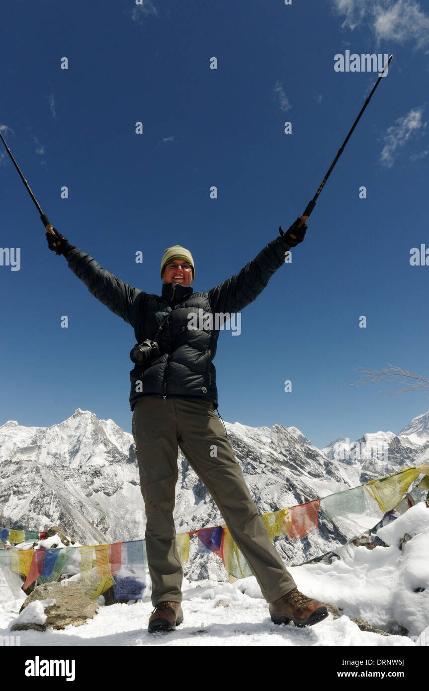 A lady trekker celebrates arriving at the summit of Gokyo Ri, Nepal himalaya - Stock Image