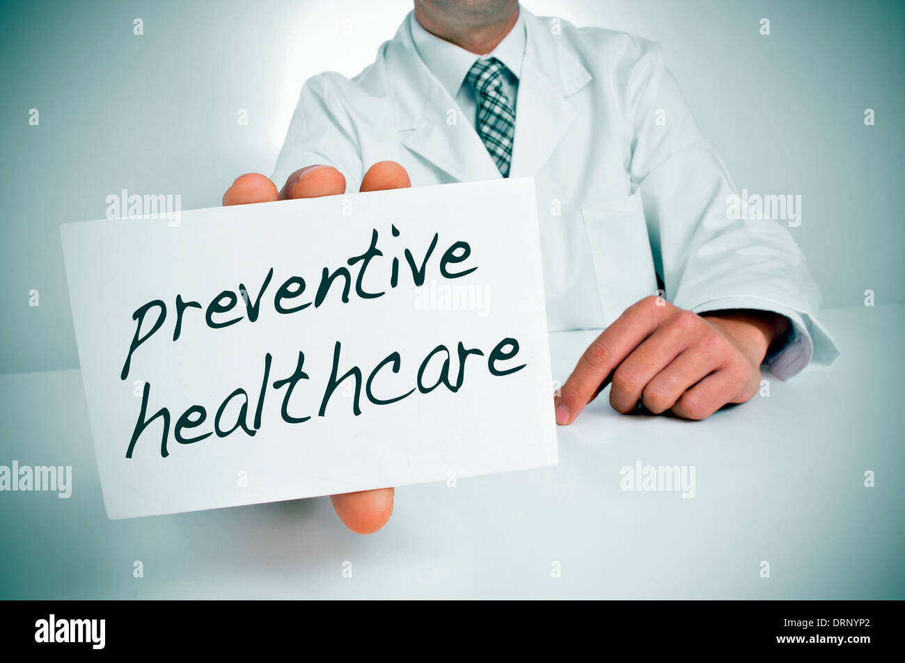 a man wearing a white coat showing a signboard with the text preventive healthcare written in it - Stock Image