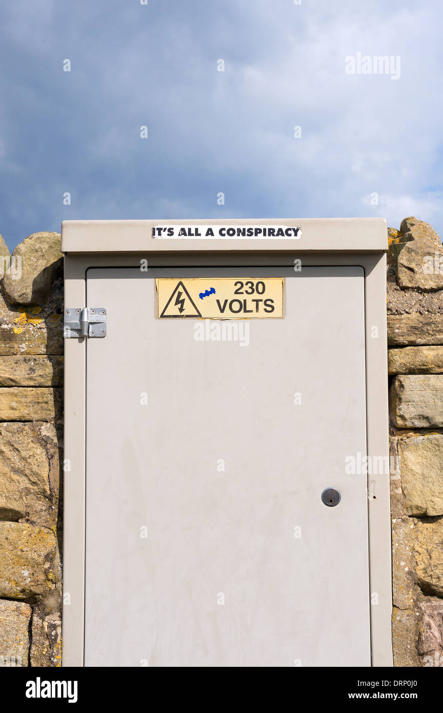 Sticker on an electricity box terminal. 'It's All A Conspiracy' against a stone wall with blue sky in the background - Stock Image