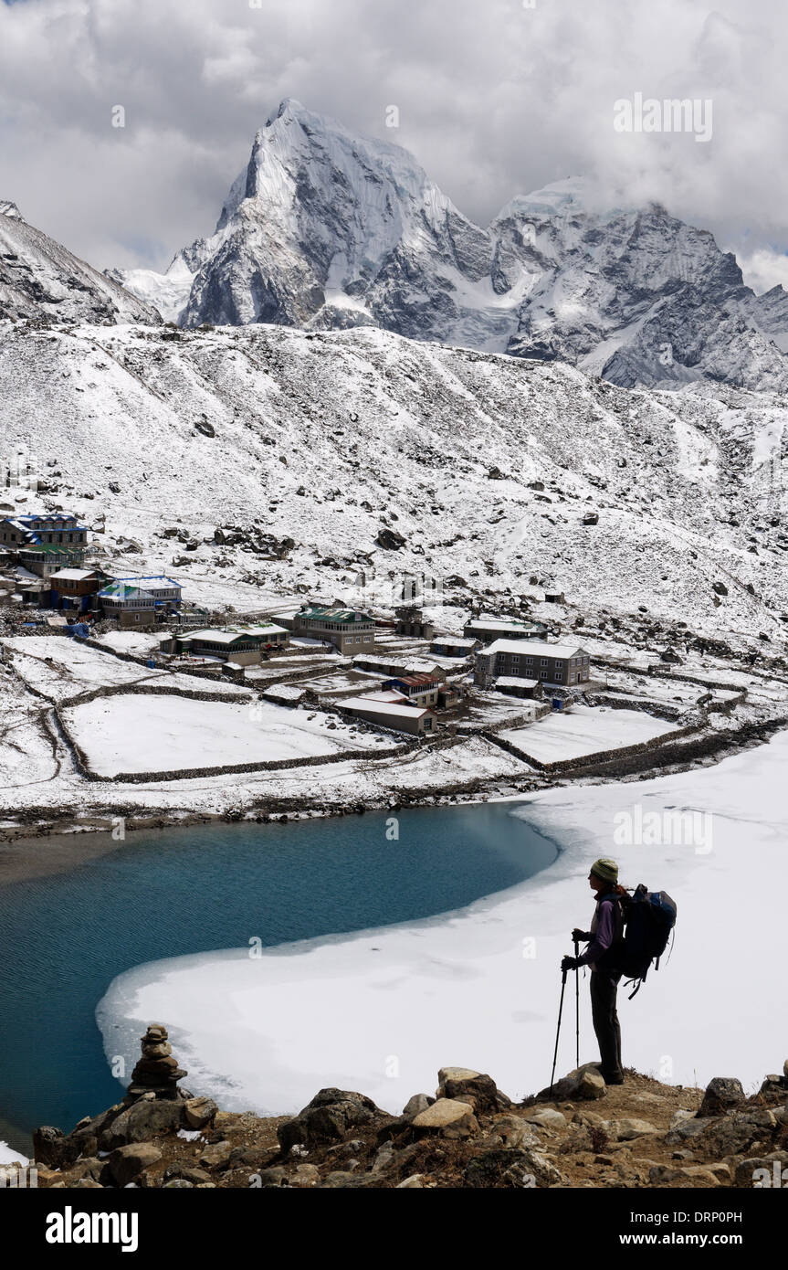 A lady trekker on the ascent to Gokyi Ri, with the Gokyo Lakes below - Stock Image