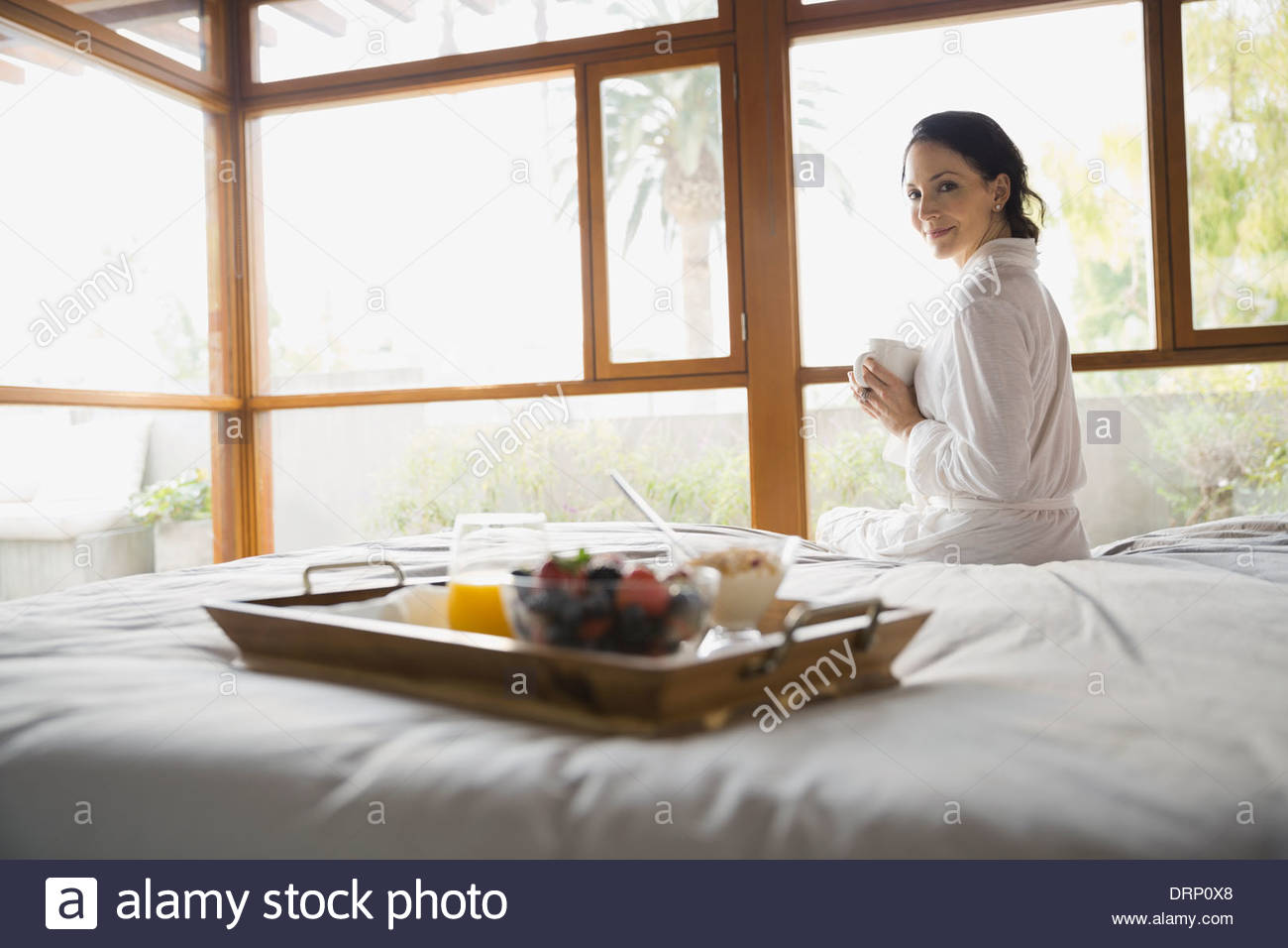 Woman sitting on bed holding coffee cup Stock Photo