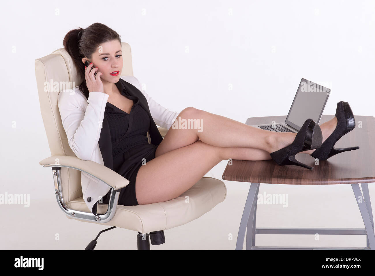 secretary using a telephone sitting at her desk with her feet up