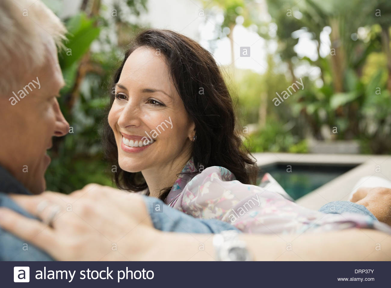 Smiling couple looking at each other outdoors - Stock Image