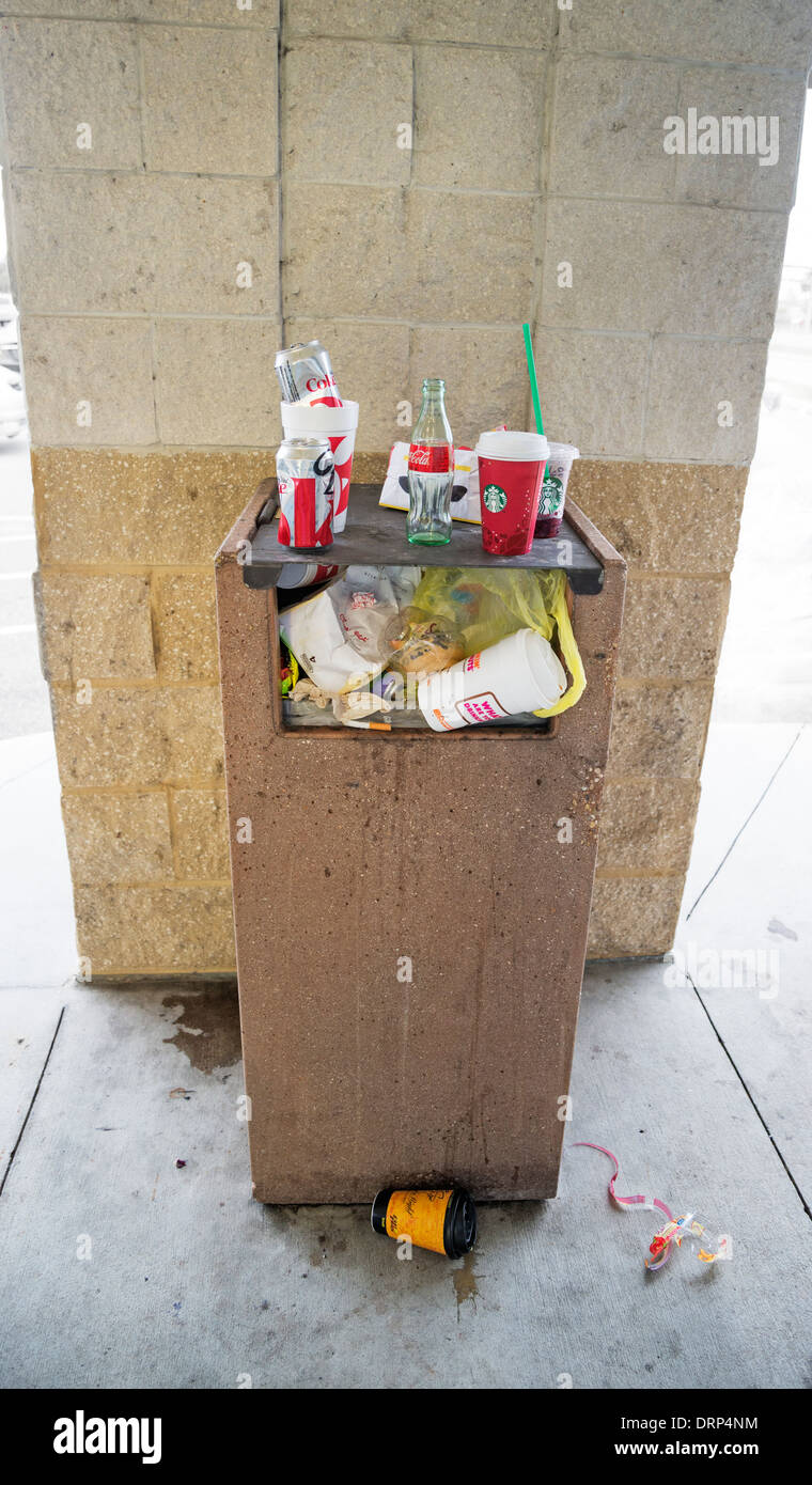 Trash receptacle overloaded in shopping mall. - Stock Image