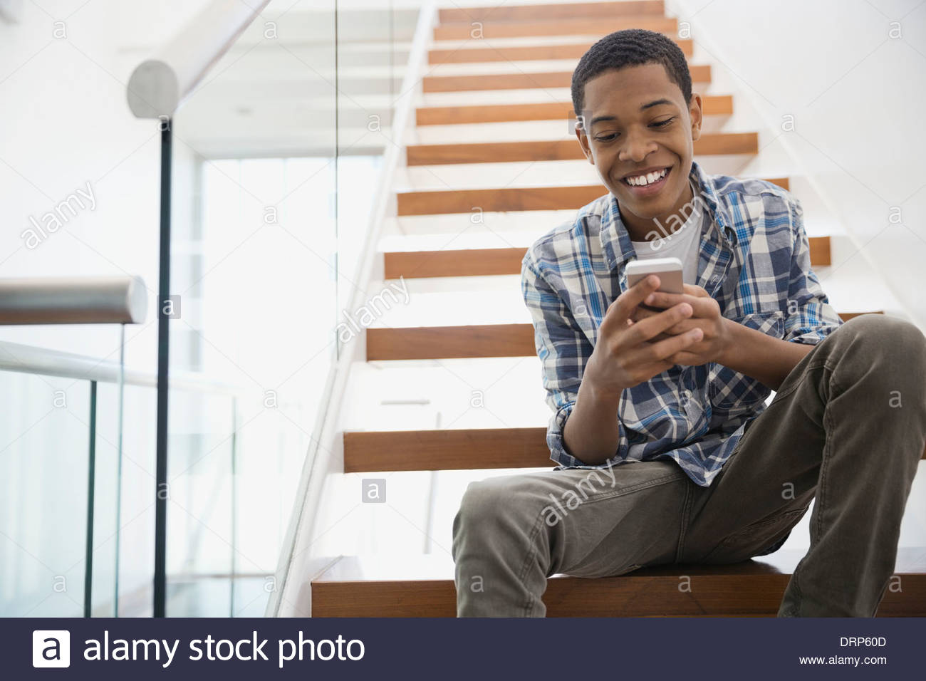 Teen using smart phone on steps at home - Stock Image