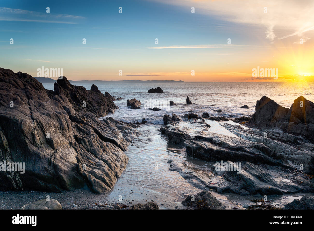 Sunrise at a rock beach at Looe in Cornwall Stock Photo