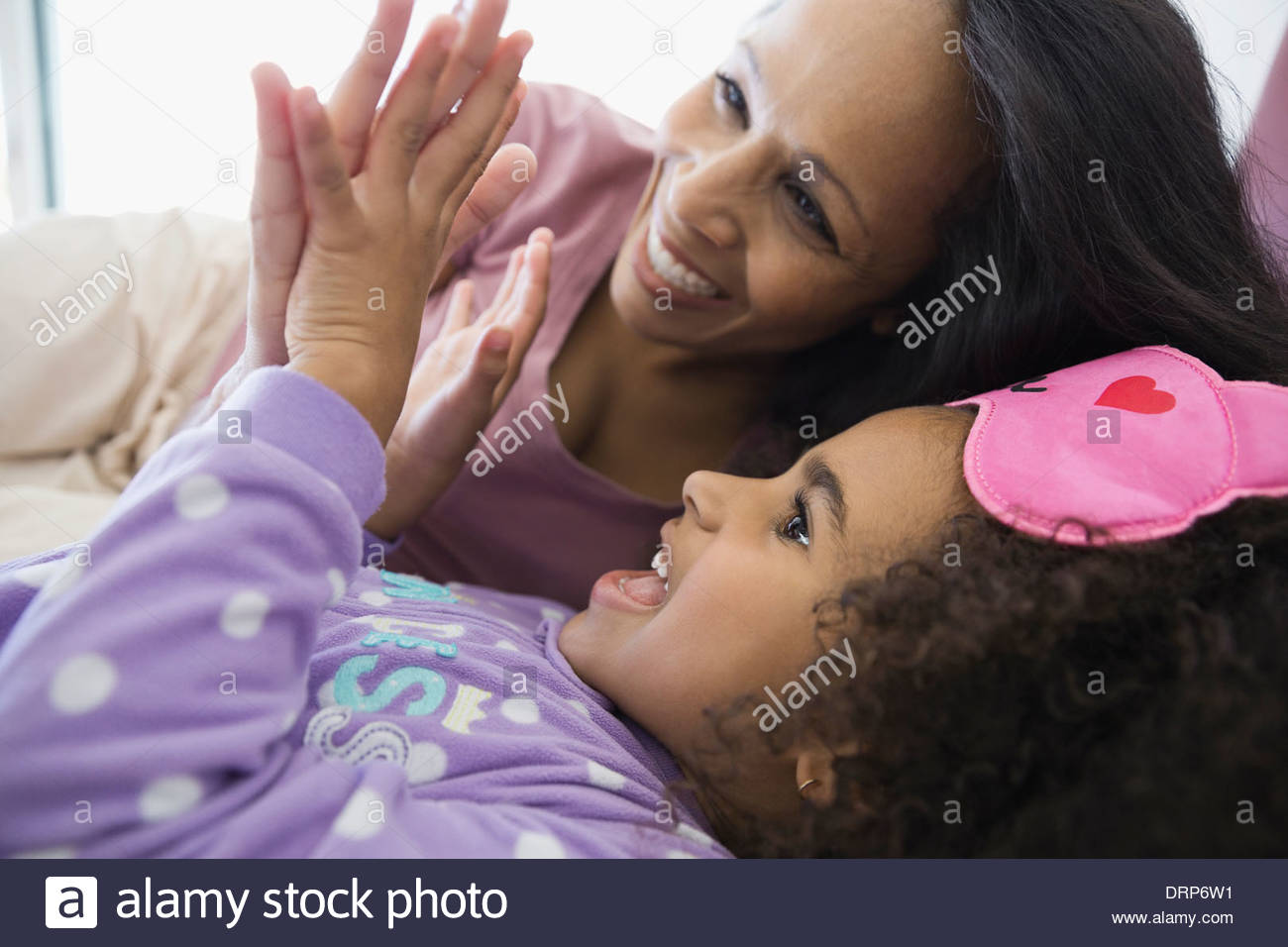 Playful mother and daughter at home - Stock Image