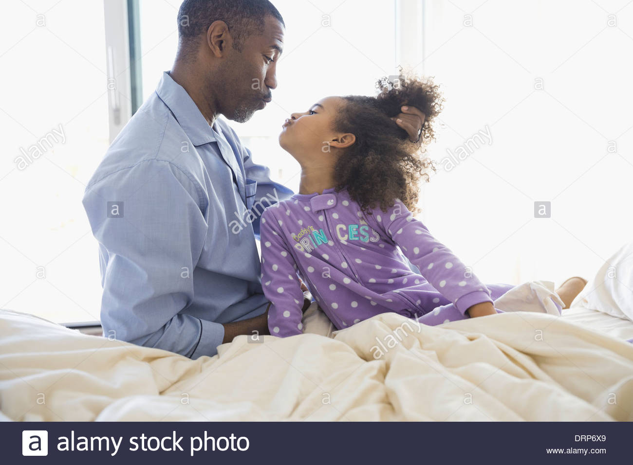 Playful father and daughter looking at each other - Stock Image