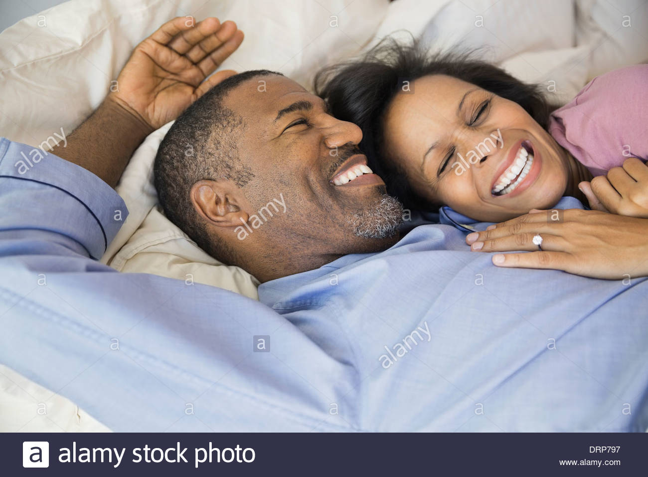 Cheerful couple resting in bed - Stock Image