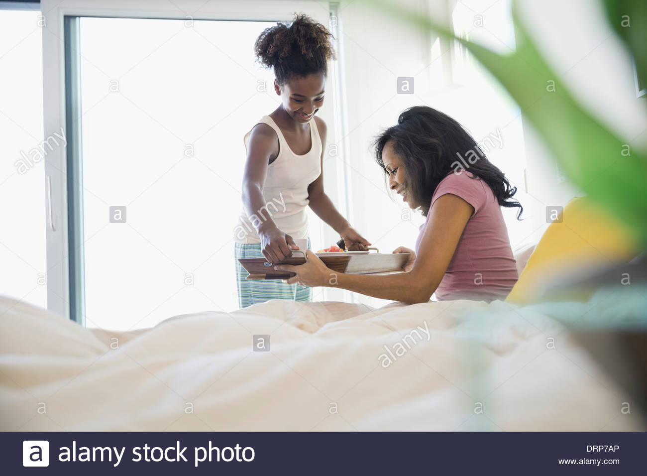 Daughter giving breakfast to mother in bed - Stock Image