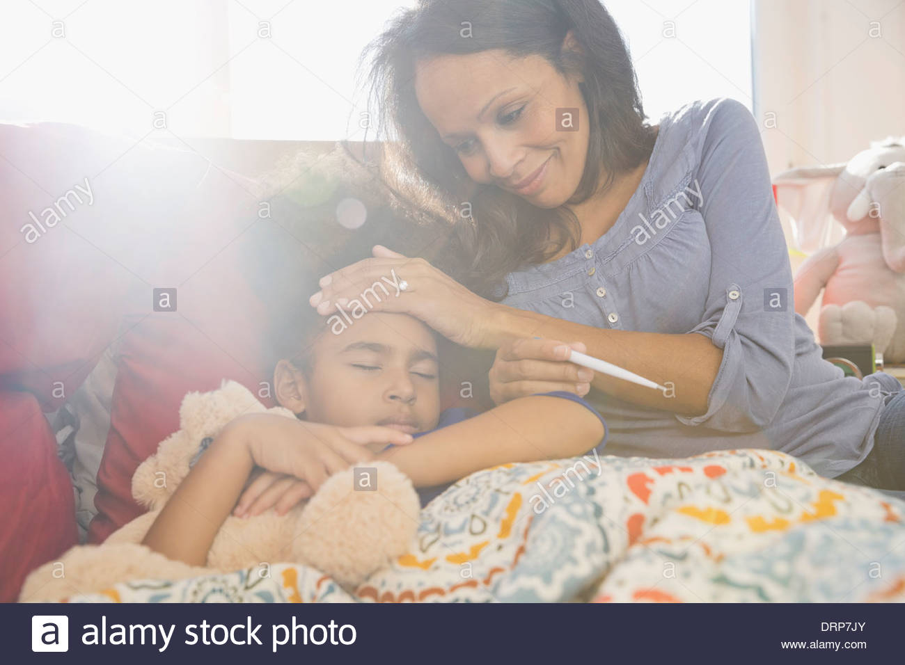 Mother checking daughters temperature - Stock Image