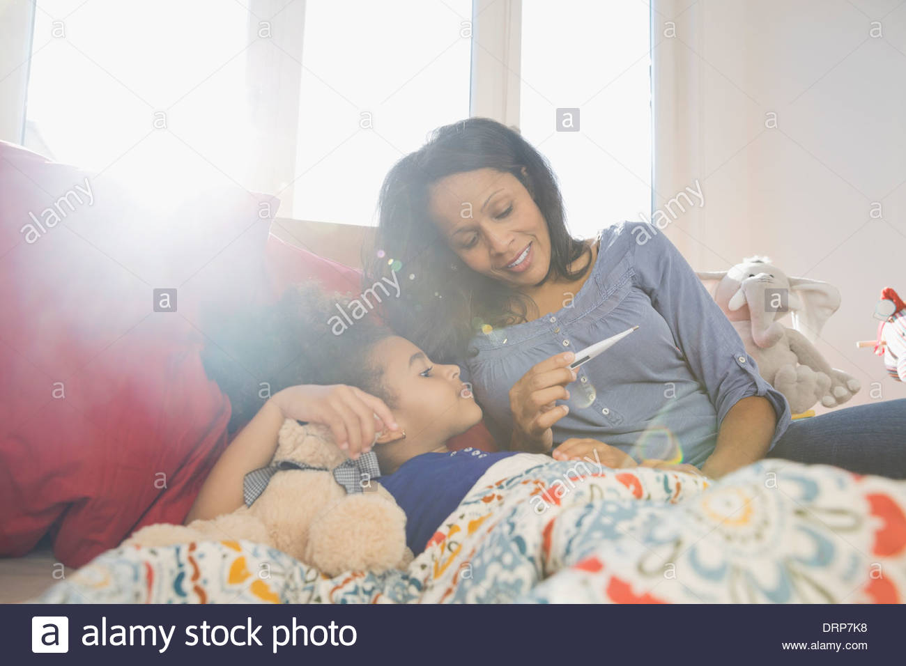 Mother checking daughters temperature with thermometer - Stock Image