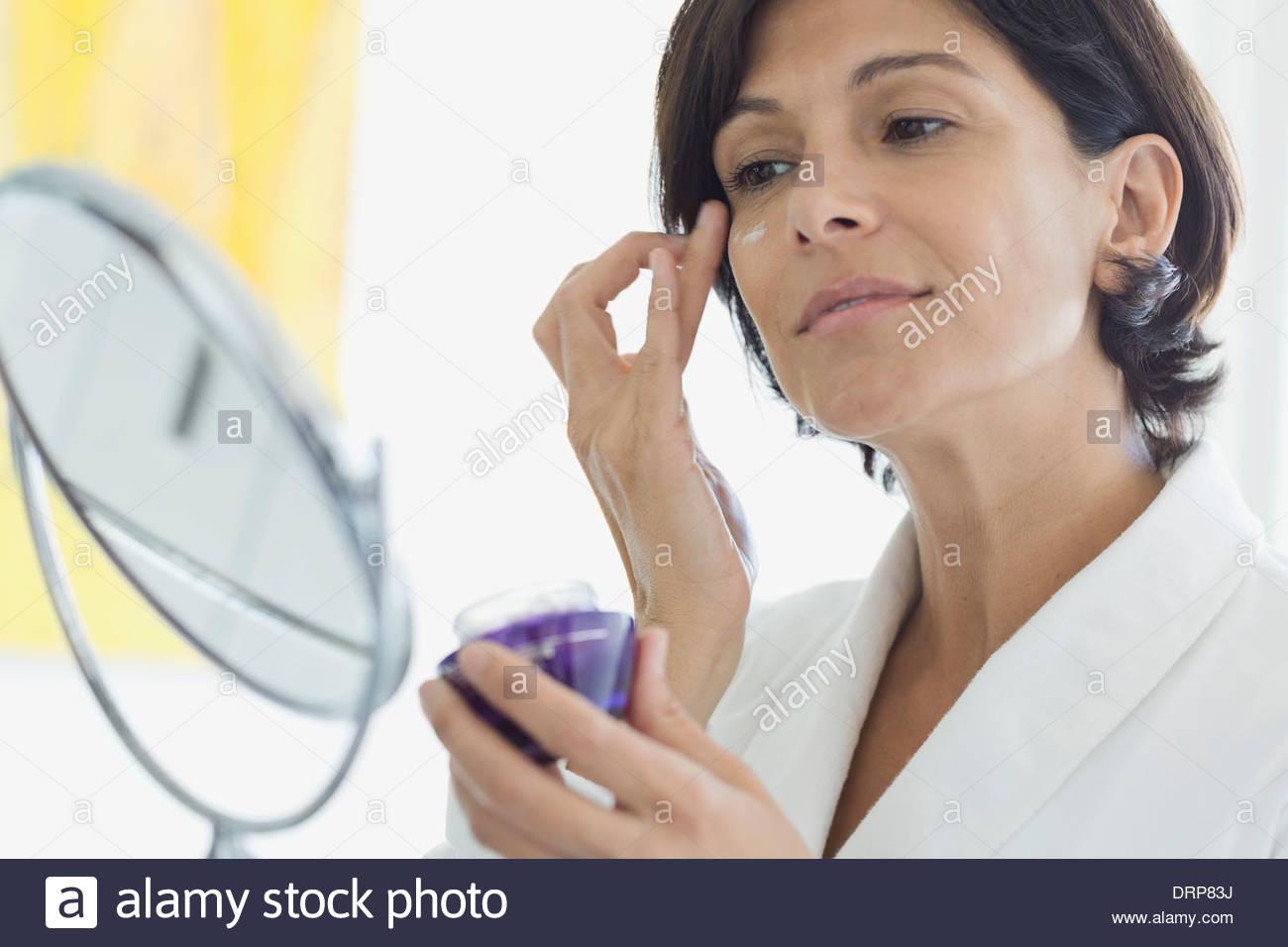 Woman applying eye cream - Stock Image