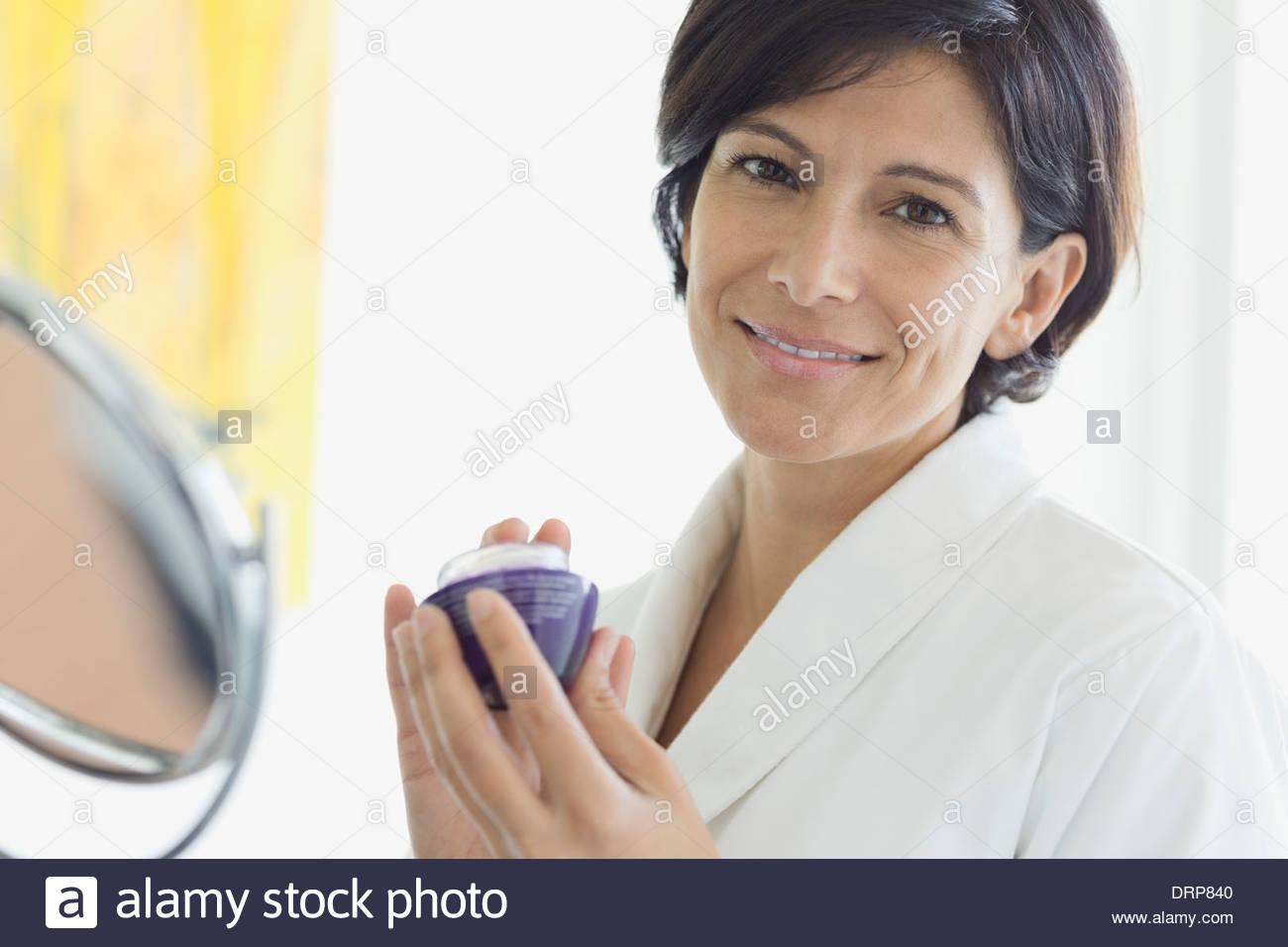 Woman holding eye cream in bathroom - Stock Image