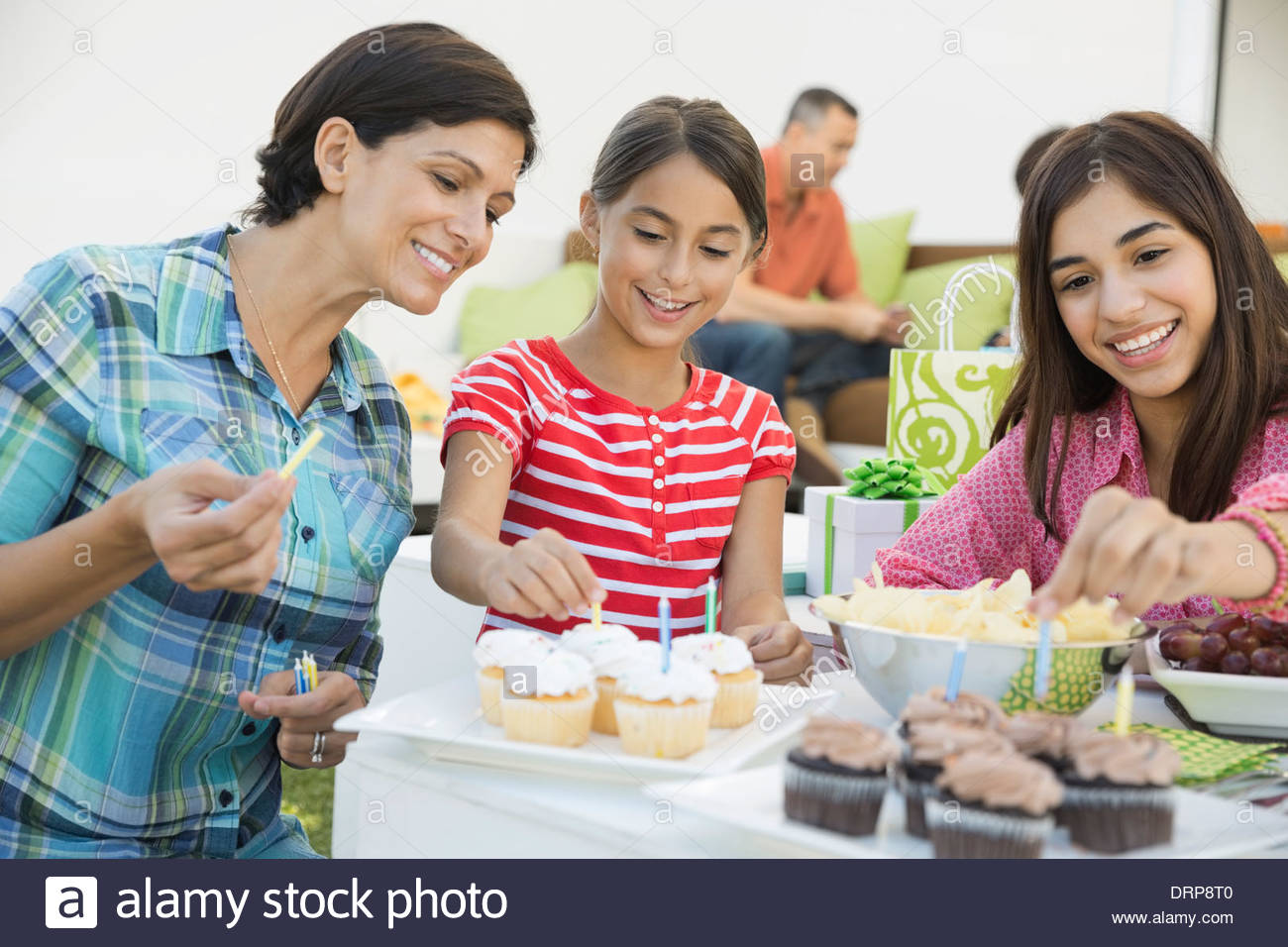 Mother and daughters placing candles in cupcakes - Stock Image