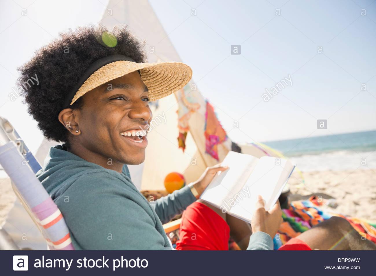 Cheerful man reading book on beach - Stock Image