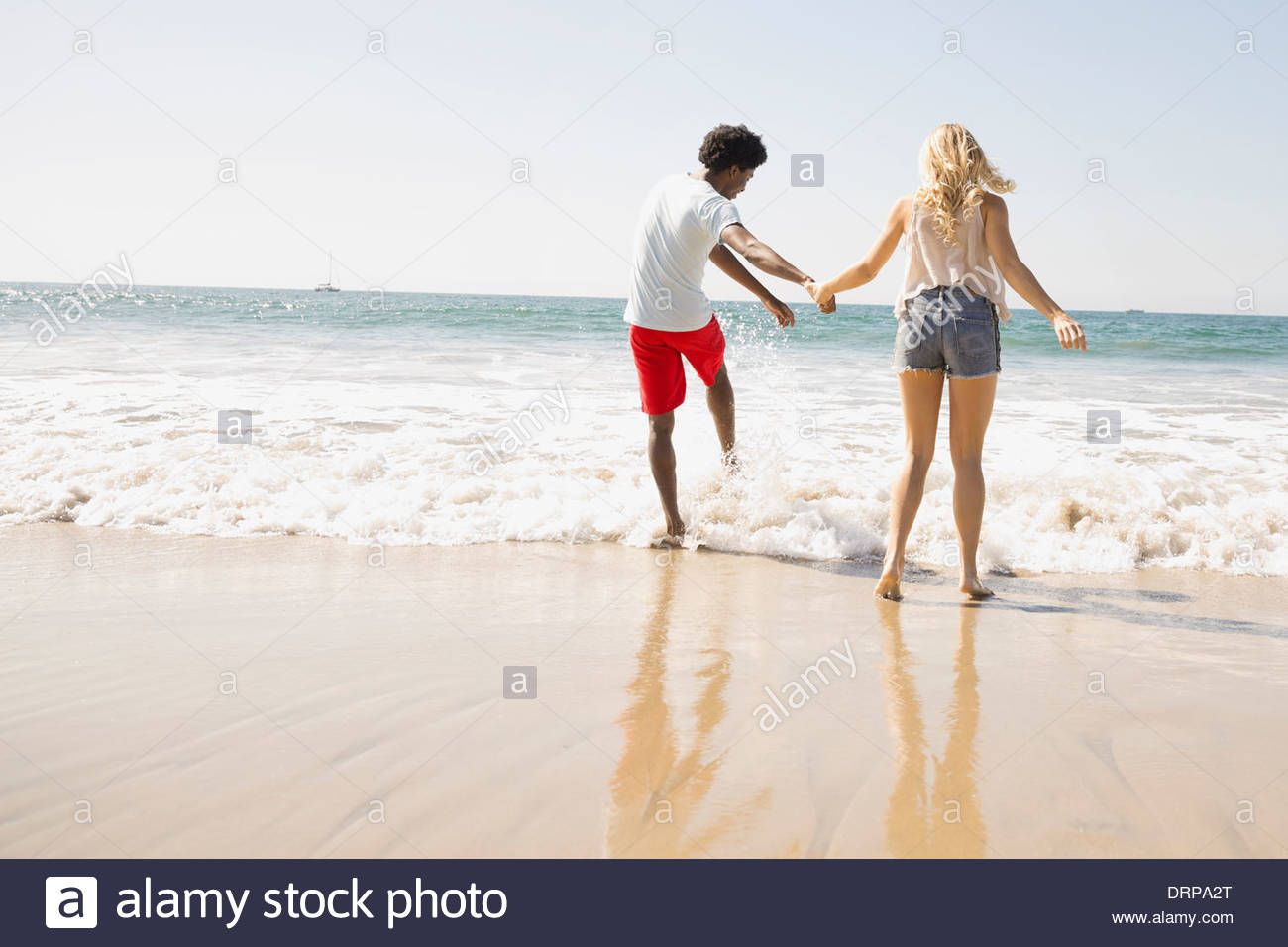 Couple wading in the surf Stock Photo