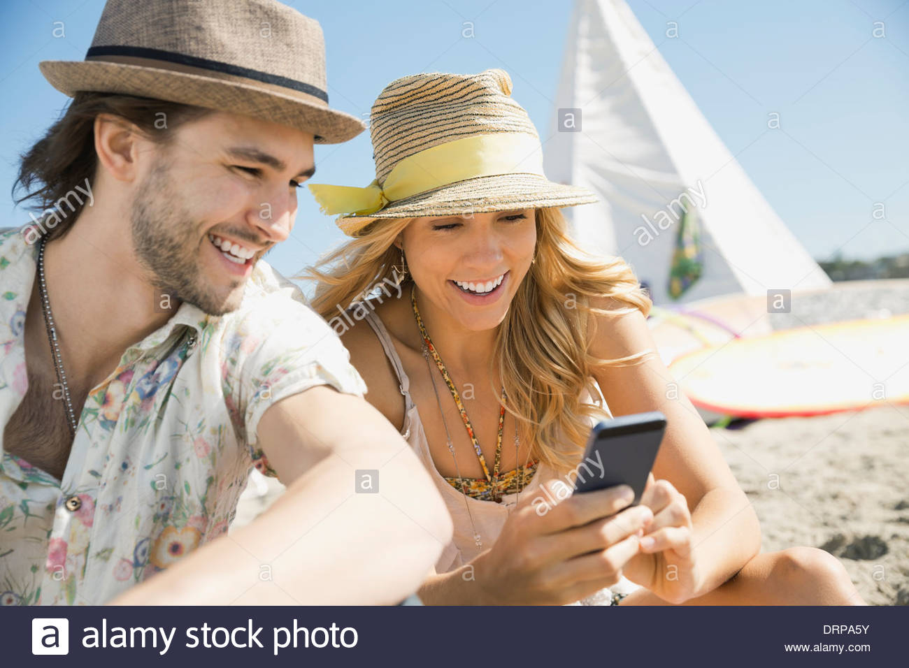 Couple using smart phone together on beach - Stock Image