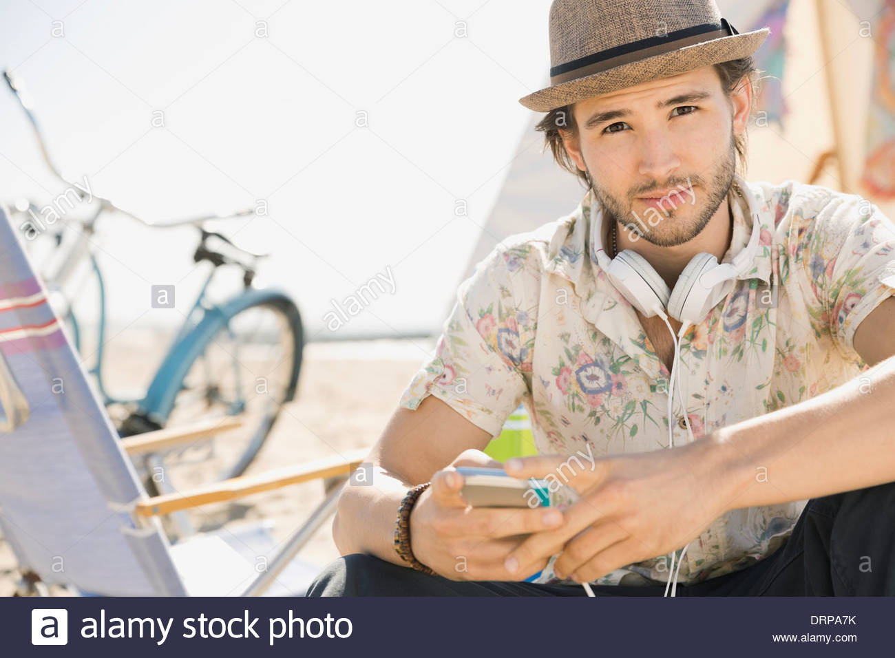 Portrait of man with smart phone on beach - Stock Image