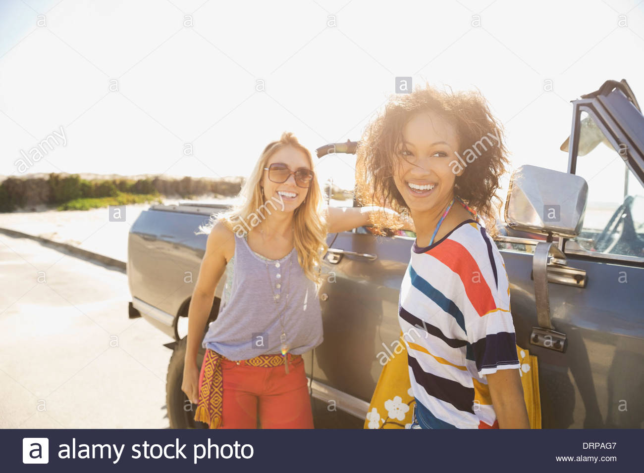 Female friends standing by off-road vehicle - Stock Image